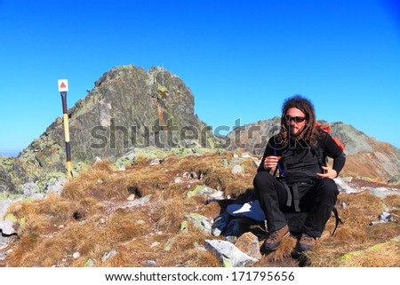 Mountaineer sitting near the mountain summit - stock photo