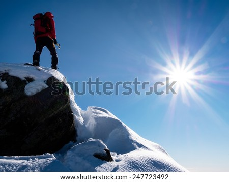 Mountaineer standing at the top of the mountain. Sunny winter day. Italian Alps, Europe. - stock photo