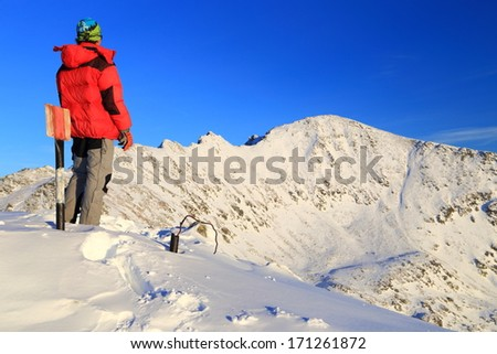 Mountaineer stands on the snowy mountain under sunset light - stock photo