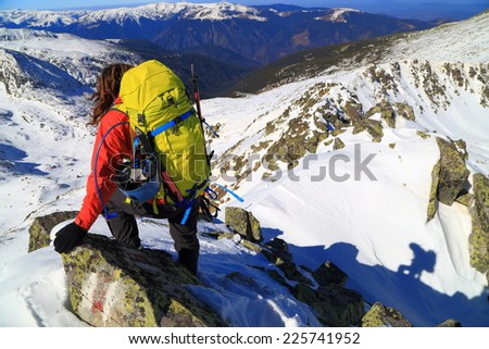 Mountaineer traversing a difficult ridge covered with snow - stock photo
