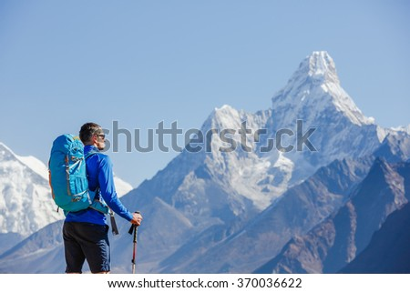 Mountaineer with backpack reaches the top on sunny day