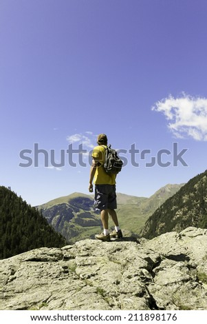 mountaineer with backpack standing enjoying the view of the landscape on the top of the mountain Pyrenees Aragon Spain - stock photo