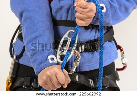 Mountaineer with climbing equipment. Young female rock climber wearing safety harness pulling climbing rope - stock photo