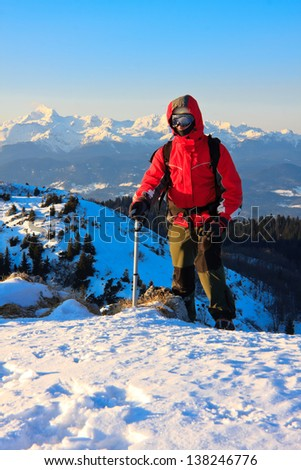 Mountaineer with ice axe arriving on top of the Altemaver on Ratitovec mountain with a view of Alps, Slovenia - stock photo