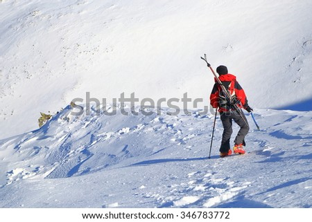 Mountaineer woman carries skis on the backpack while descending ice covered slope - stock photo