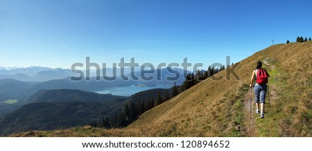 mountaineering woman, back view, walking towards the summit cross, beautiful panoramic view over bavarian alps and lake - stock photo