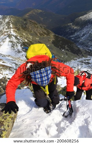 Mountaineers ascending a steep gully in winter - stock photo