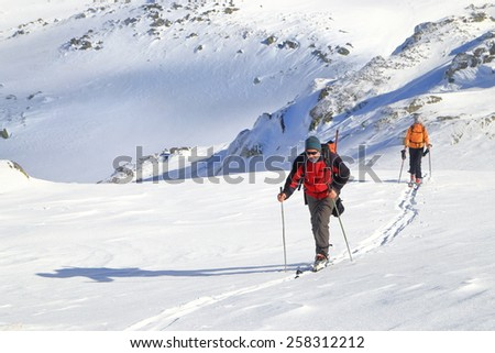 Mountaineers ascending on snow covered trail while carrying skies on the backpack - stock photo