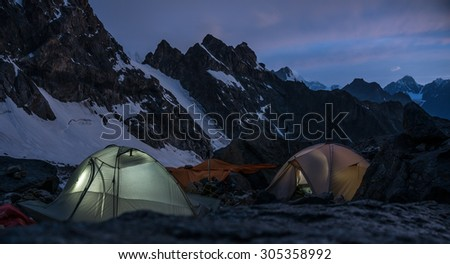 Mountaineers bivouac at night in very high snowy mountains. Picture was taken during a trekking hike in wonderful  mountains of northern Caucasia , Bezengi region, Kabardino-Balkaria, Russia - stock photo