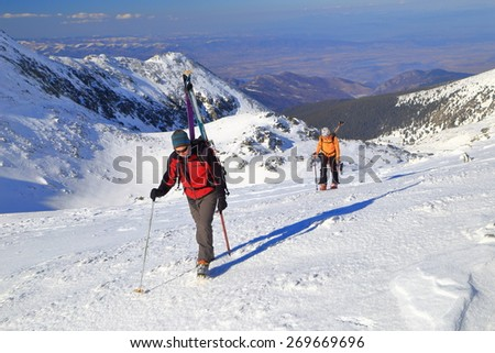 Mountaineers carrying backpacks with touring skies on sunny slope covered with snow - stock photo