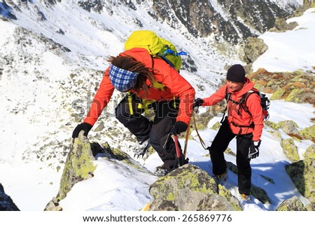 Mountaineers climbing mixed trail on snow covered mountains - stock photo