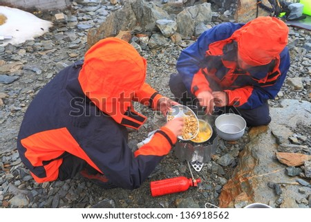 Mountaineers cooking during bad weather - stock photo