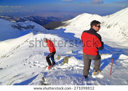 Mountaineers descend a snow covered ridge in sunny winter day - stock photo