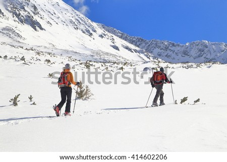 Mountaineers traversing a mountain on touring skis in sunny winter day - stock photo