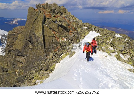 Mountaineers walking in a row along snow covered ridge - stock photo