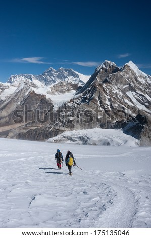 Mountaineers walking on snow with Mt. Everest, Himalayas of Nepal - stock photo