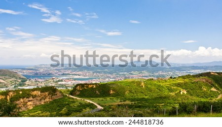 Mountainous landscape with city in the bottom on a cloudy day in the Basque Country - stock photo