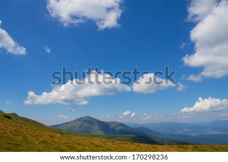 mountains and blue cloudy sky background - stock photo