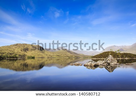 mountains and blue sky reflecting in the water of loch on rannoch moor in the highlands of scotland - stock photo