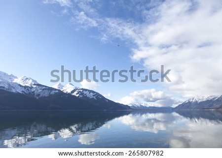 Mountains and clouds reflected in the still water of the Chilkat Inlet in Southeast Alaska. - stock photo