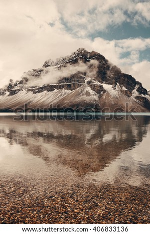 Mountains and forest reflection at Bow Lake with fog in Banff National Park, Canada. - stock photo