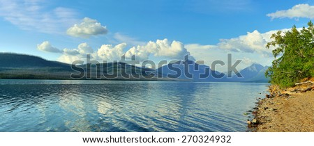 Mountains and reflection of clouds in McDonald lake in Glacier National Park, Montana in summer - stock photo