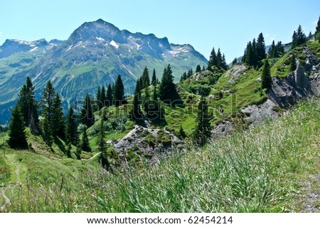 Mountains in Austrian alps with hiking tourists - stock photo