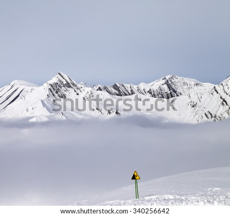 Mountains in mist and warning sing on ski slope. Caucasus Mountains, Georgia, ski resort Gudauri. - stock photo