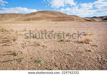 Mountains in the distance of the desert valley with dry soil under the scorching sun of the Middle East - stock photo