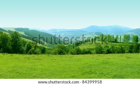 Mountains Landscape with Grass Meadow on Foreground - stock photo