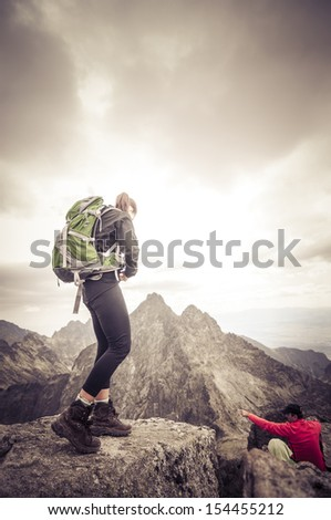 Mountains landscape. Young tourist woman walking the trail in the green mountains. Standing on the ridge or edge. - stock photo