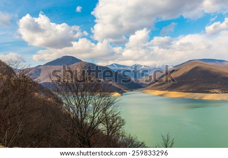 Mountains near the green lake and sky with clouds
