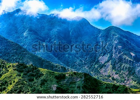 Mountains or rock with clouds over peak