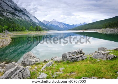 Mountains reflecting in Medicine Lake in Jasper National Park, Canada - stock photo