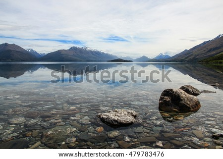 Mountains reflecting in water of Lake Wakatipu, on the way to Glenorchy, New Zealand, with rocks in the foreground.