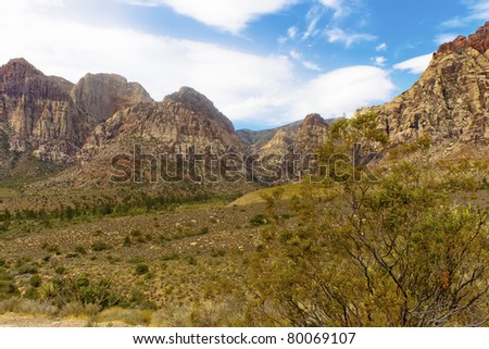 Mountains rising from desert covered with green scrub brush - stock photo