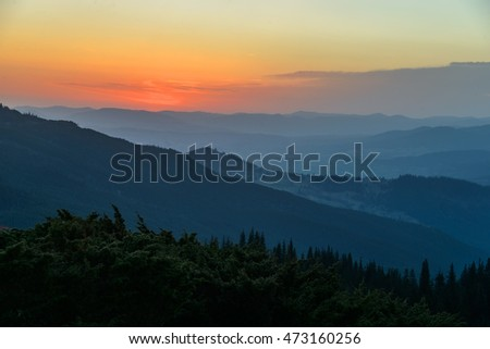 Mountains silhouettes are seen through morning fog. Bright red and yellow sky in background.