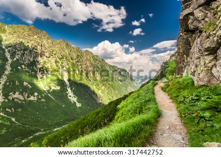 Mountains trail leading the peak at summer - stock photo
