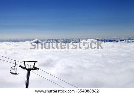 Mountains under clouds and chair-lift. View from ski slope. Caucasus Mountains, Georgia, region Gudauri. - stock photo