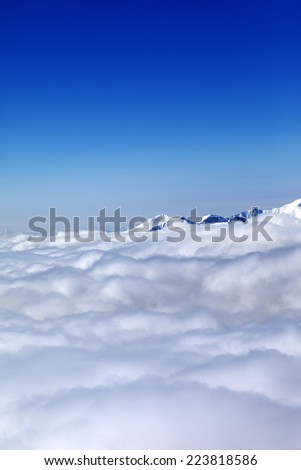 Mountains under clouds and clear blue sky. Caucasus Mountains, Georgia, Gudauri. View from ski slope.
