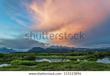 Mountains with pink cloud overhead - stock photo