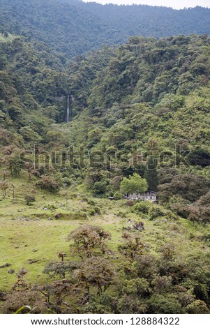 Mountainside in the Amazonian foothills of the Andes in Ecuador deforested for cattle pasture, with forested ravine and waterfall - stock photo