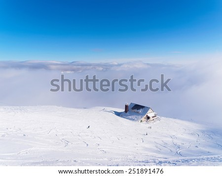 Mountaintop chalet in a winter day - stock photo