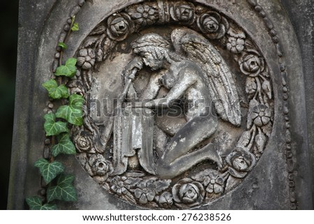 Mourning angel depicted in the abandoned tombstone at the Malostransky Cemetery in Prague, Czech Republic. - stock photo