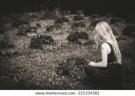 Mourning girl at cemetery, Selective focus. - stock photo