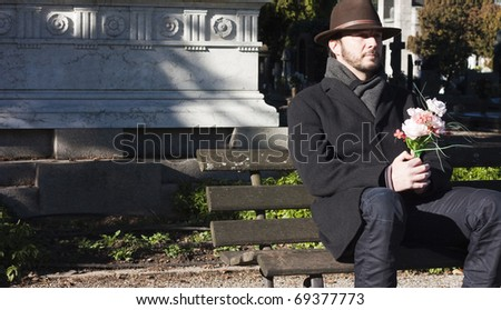 Mourning Man Seating on a Bench in a Graveyard
