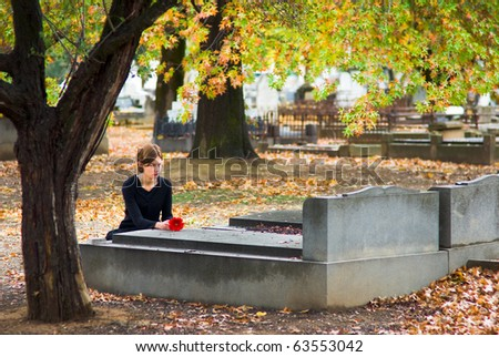 Mourning Woman Laying Flower on Grave in Cemetery in Fall - stock photo