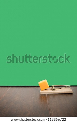 Mousetrap set with cheddar cheese on a floor, next to a mouse hole. - stock photo