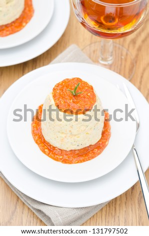 mousse of chicken with pumpkin, green and red pepper sauce on a plate top view closeup