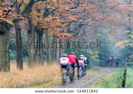 Moutain bikers, cyclist, speeding in beautifully colored autumn wood, unrecognizable by motion blur - stock photo